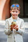 Cute little boy holding his pet baby goose royalty free stock photos
