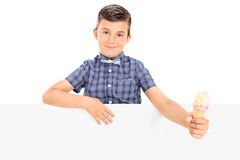Cute little boy holding an ice cream behind a panel Royalty Free Stock Photos