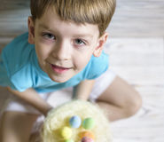 Cute little boy holding a nest with colored Easter eggs at home on Easter day. Celebrating Easter at spring. Painting eggs Royalty Free Stock Photography