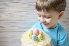 Cute little boy holding a nest with colored Easter eggs at home on Easter day. Celebrating Easter at spring. Painting eggs Stock Image