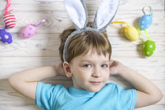 Cute little boy holding a nest with colored Easter eggs at home on Easter day. Celebrating Easter at spring. Painting eggs Stock Photography