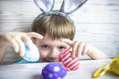 Cute little boy holding a nest with colored Easter eggs at home on Easter day. Celebrating Easter at spring. Painting eggs Royalty Free Stock Photo
