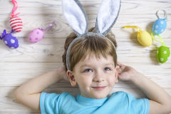 Cute little boy holding a nest with colored Easter eggs at home on Easter day. Celebrating Easter at spring. Painting eggs Stock Images
