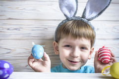 Cute little boy holding a nest with colored Easter eggs at home on Easter day. Celebrating Easter at spring. Painting eggs Royalty Free Stock Images