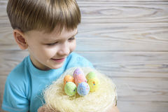 Cute little boy holding a nest with colored Easter eggs at home on Easter day. Celebrating Easter at spring. Painting eggs Stock Photo