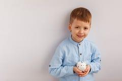 Cute little boy holding a piggy bank or money box. Stock Photo