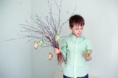 Cute little boy holding pussy willow twigs with hanging easter eggs Stock Photo