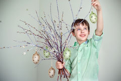 Cute little boy holding pussy willow twigs with hanging easter eggs Royalty Free Stock Photo