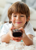 Cute little boy holding a remote lying Stock Photos