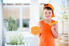 Cute little boy holding sliced orange cantaloupe melon in hands Royalty Free Stock Photos