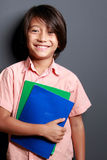 Cute little boy holding some books Stock Photo