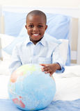 Cute little boy holding a terrestrial globe. Lying on his bed royalty free stock images