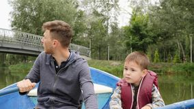 Cute little boy holds oar and helps rowing his young father. Happy young father having fun with his little son. Lovely young daddy. And son enjoying time stock video footage