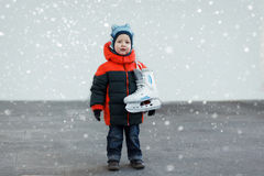 Cute little boy  holds the skates wearing warm winter clothes  g Royalty Free Stock Image