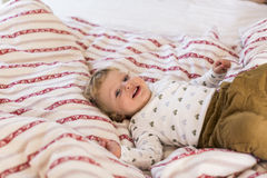 Cute little boy at home lying on bed smiling. Royalty Free Stock Images