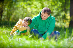 Cute little boy hugs his father outdoors Stock Image