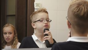 Cute little boy imitates shaving a beard with electric razor stock video footage