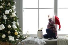 Free Cute Little Boy In Santa Hat On Window Sill Near Christmas Tree At Home Stock Photo - 208127640