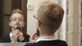 Smart boy imitates shaving on his face stock footage