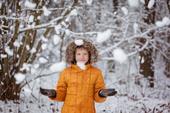 Cute little boy, kid in winter clothes walking under the snow in winter park royalty free stock images