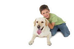 Cute little boy kneeling with his labrador smiling at camera Royalty Free Stock Photo
