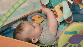 Cute little boy lays in children`s tent and playing with soft toys stock video
