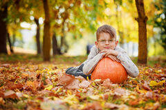 Cute little boy  leaning on a pumpkin, autumn time. Stock Image