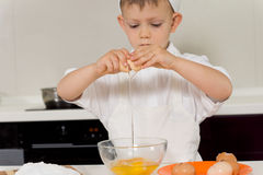 Cute little boy learning to bake a cake Stock Photos