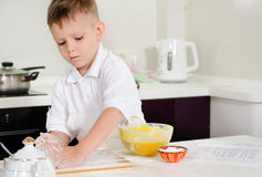 Cute little boy learning to bake cakes Royalty Free Stock Photos