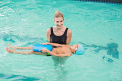 Cute little boy learning to swim with coach Royalty Free Stock Photography
