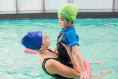 Cute little boy learning to swim with coach. At the leisure center Stock Image