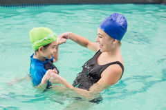 Cute little boy learning to swim with coach Stock Images