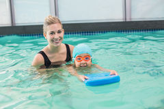 Cute little boy learning to swim with coach Royalty Free Stock Photos