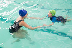 Cute little boy learning to swim with coach Stock Photography