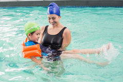 Cute little boy learning to swim with coach. At the leisure center Royalty Free Stock Photos