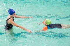 Cute little boy learning to swim with coach. At the leisure center Stock Photography