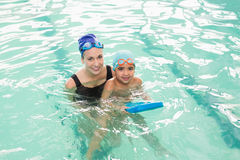 Cute little boy learning to swim with coach Royalty Free Stock Image