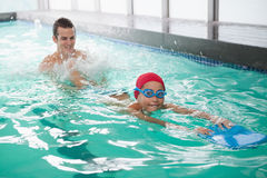 Cute little boy learning to swim with coach Royalty Free Stock Photo