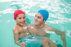 Cute little boy learning to swim with coach Stock Photos