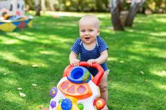 Cute little boy learning to walk with walker toy on green grass lawn at backyard. Baby laughing and having fun making