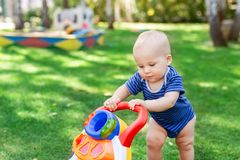 Cute little boy learning to walk with walker toy on green grass lawn at backyard. Baby laughing and having fun making stock photos