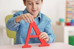 Cute little boy with letter A at speech therapist. Office royalty free stock images