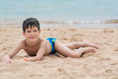 Cute little boy lies on the sand on the seashore happy,. Cute little boy lies on the sand on the seashore happy royalty free stock images