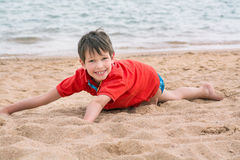 Cute little boy lies on the sand on the seashore happy,. Cute little boy lies on the sand on the seashore happy royalty free stock photo