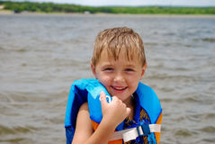 Cute little boy in life jacket on the lake. Adorable boy in a life vest smiling at the lake Royalty Free Stock Photography