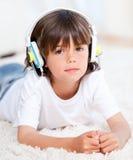 Cute little boy listening music lying on floor stock photo