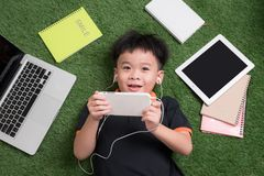 Cute little boy listens to music on the grass with his laptop, tablet and notebooks around royalty free stock photos