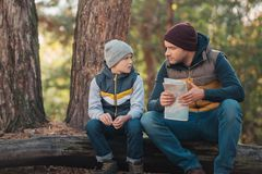 cute little boy looking at father holding map while sitting on log stock photos