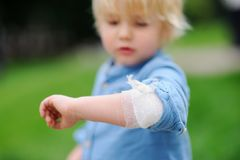 Cute little boy looking on his elbow with applied bandage. Child healthcare and medicine concept. First aid Stock Photo