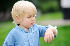 Cute little boy looking on his elbow with applied bandage. Child healthcare and medicine concept. First aid Royalty Free Stock Images